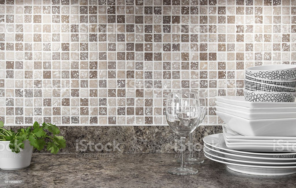 Dishware and green herbs on kitchen countertop stock photo