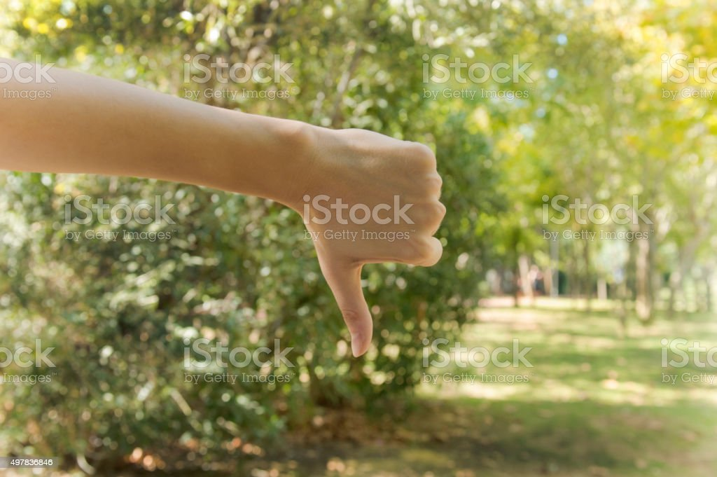 dislike hand sign isolated on tree background. stock photo