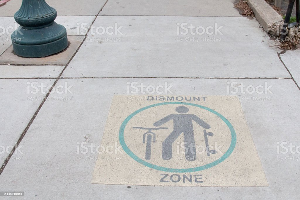 Dismount symbol on the sidewalk stock photo