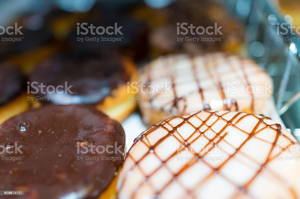 Display of chocolate and caramel glazed donuts in a bakery stock photo