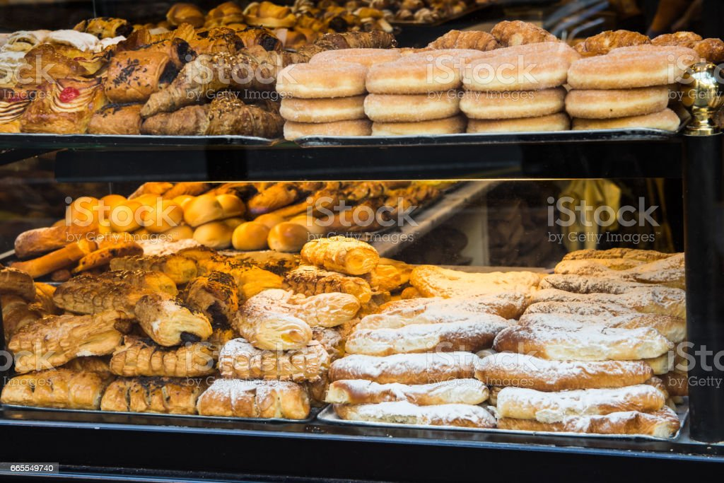 Display window of a bakery and pastry shop of a European city with variety of baked goods, breads, donuts, puff pastry stock photo