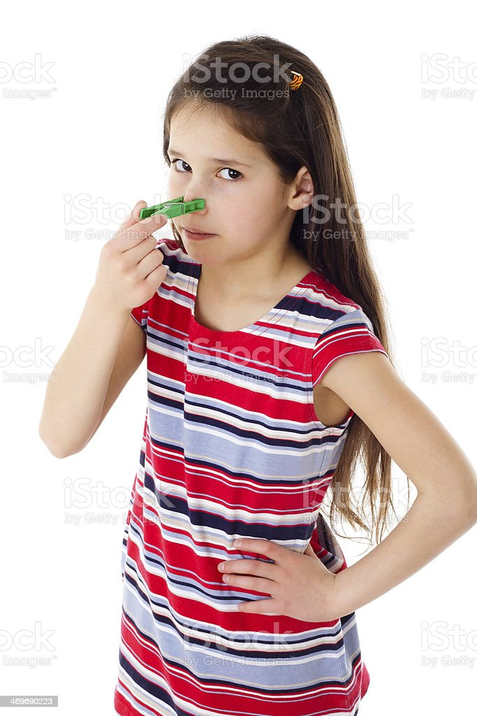 Displeased girl with clothespins on his nose stock photo