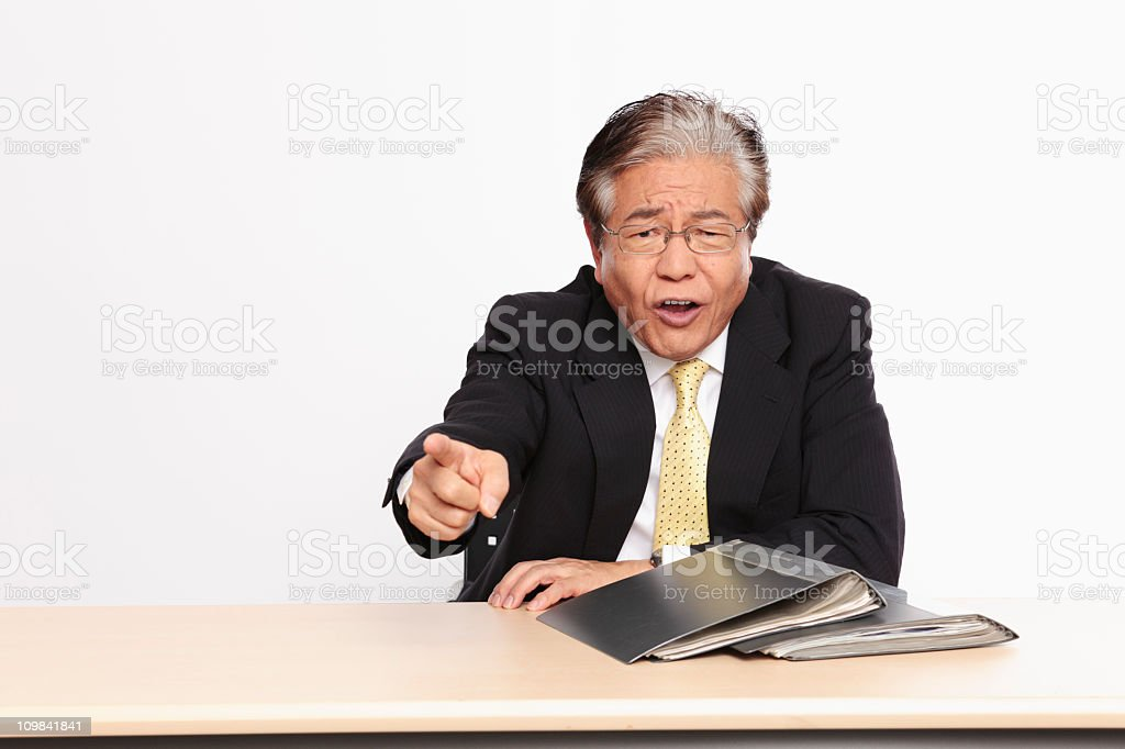Displeased Japanese Businessman sitting at his desk, pointing finger stock photo