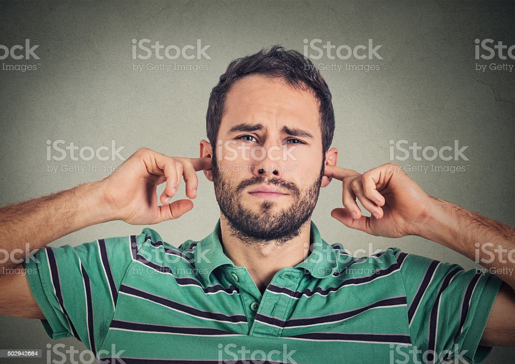 displeased man plugging ears with fingers doesn't want to listen stock photo