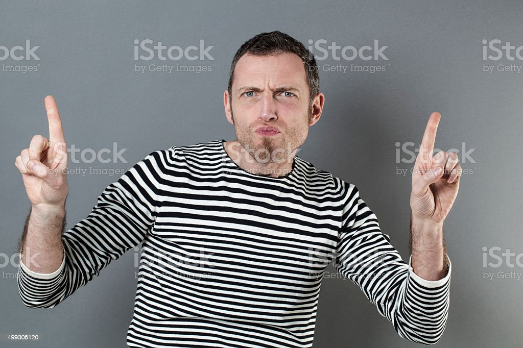 displeased man pointing up towards something with energetic body language stock photo
