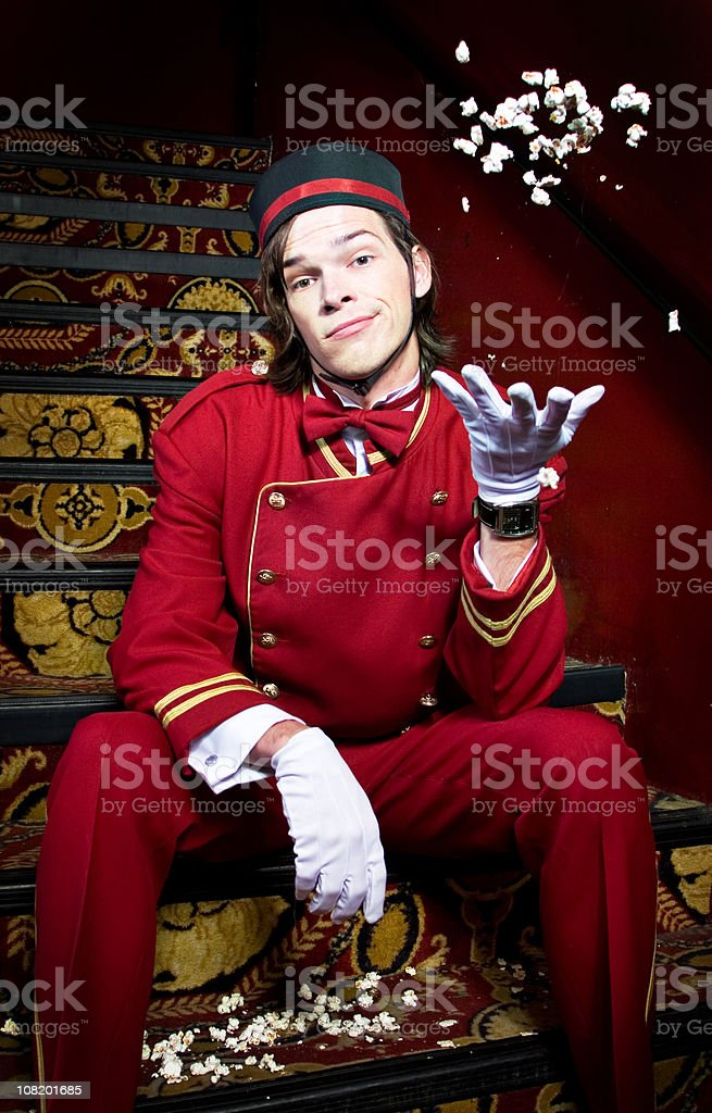 Displeased Movie Theater Usher Sitting on Stairs and Throwing Popcorn stock photo