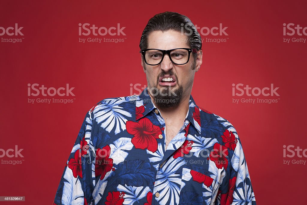 Displeased young man in Hawaiian shirt against red background royalty-free stock photo