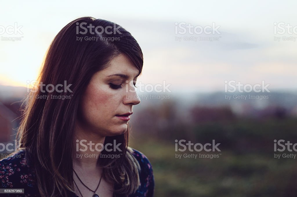 Displeased  young woman posing in a panoramic city view stock photo