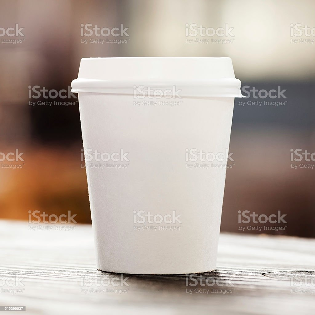 Disposable coffee cup on windowsill with city view in background stock photo