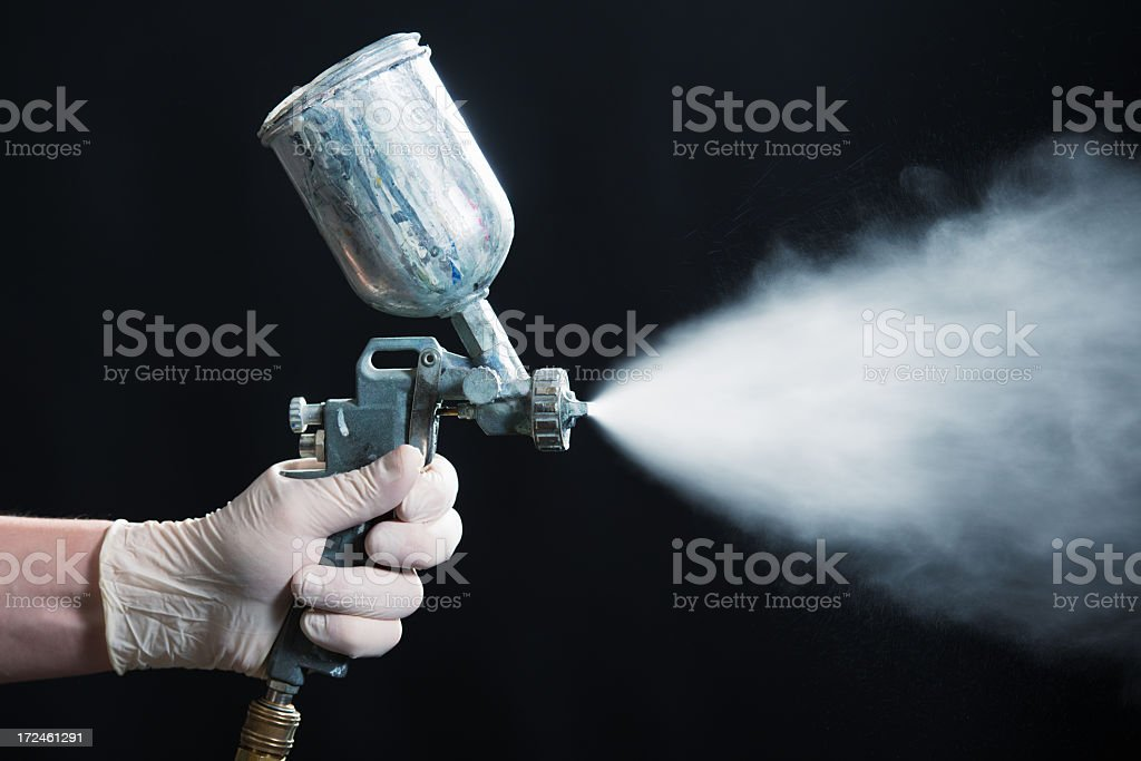 Disposable gloved hand spraying white paint from spray gun stock photo