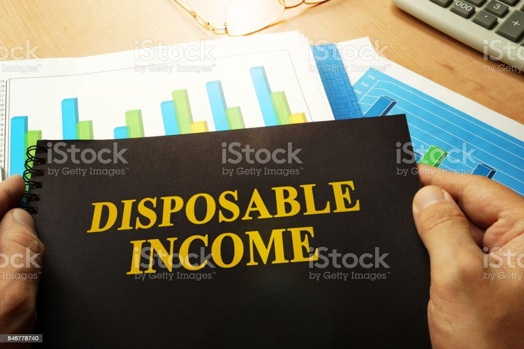 Disposable income written on a front of note. stock photo