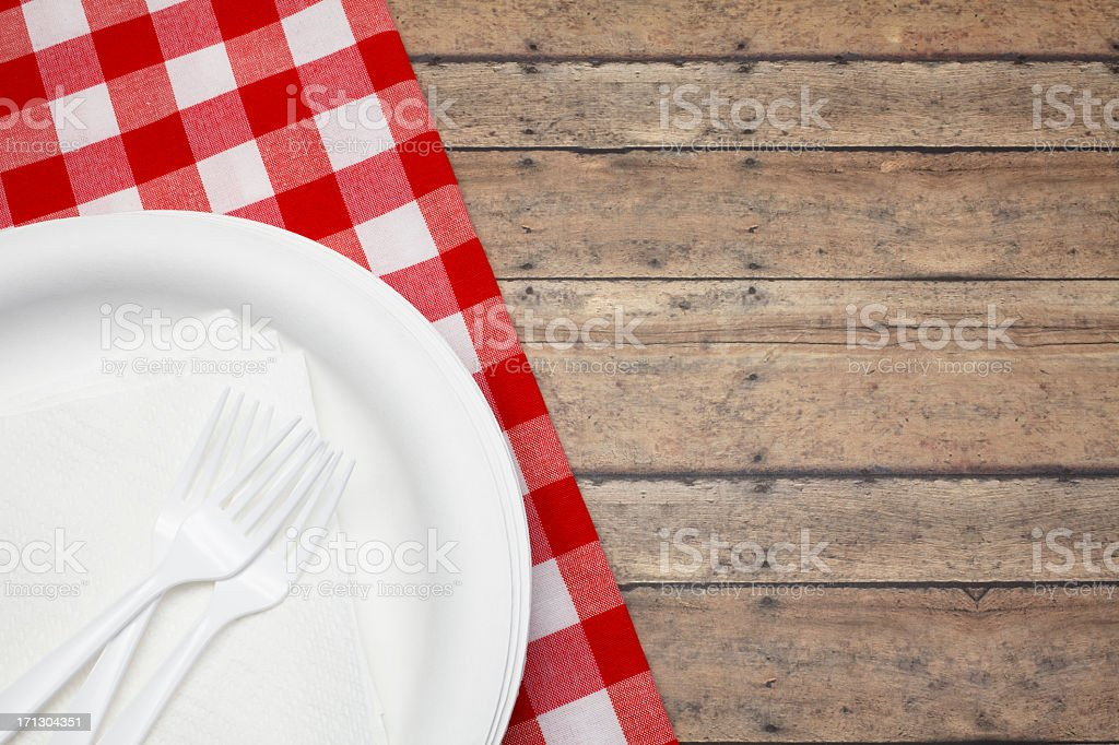 Disposable plate and forks with red and white picnic cloth stock photo