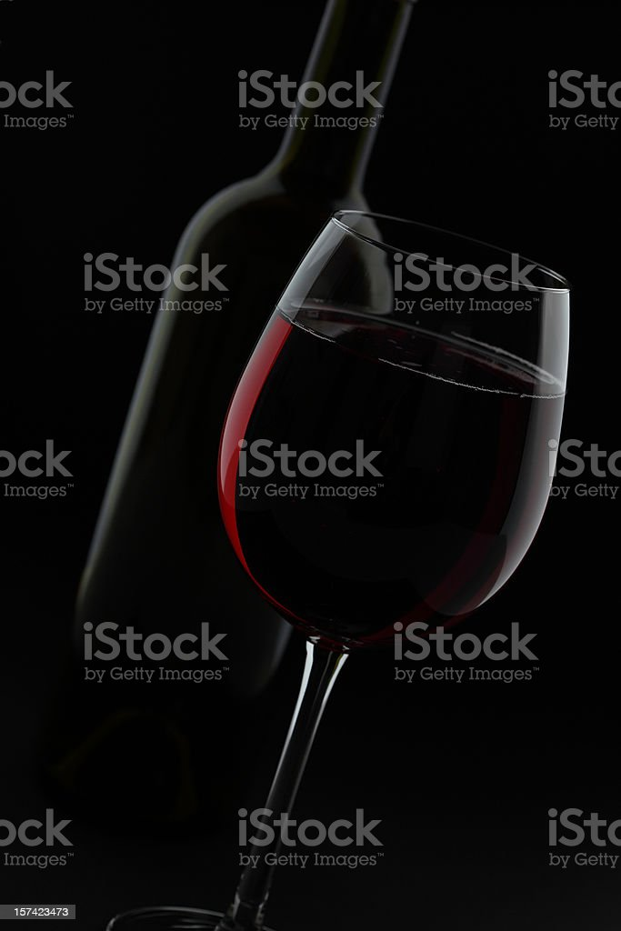 Disposed Red Wine Glass and Bottle before Black Background stock photo