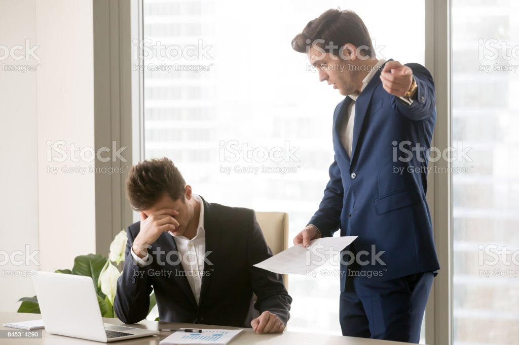 Dissatisfied annoyed boss arguing with employee stock photo