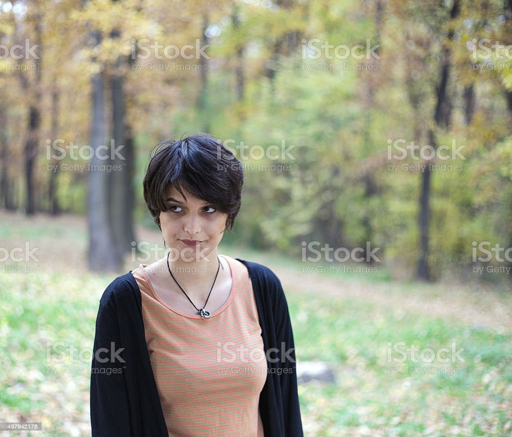 Dissatisfied young woman standing in a park royalty-free stock photo