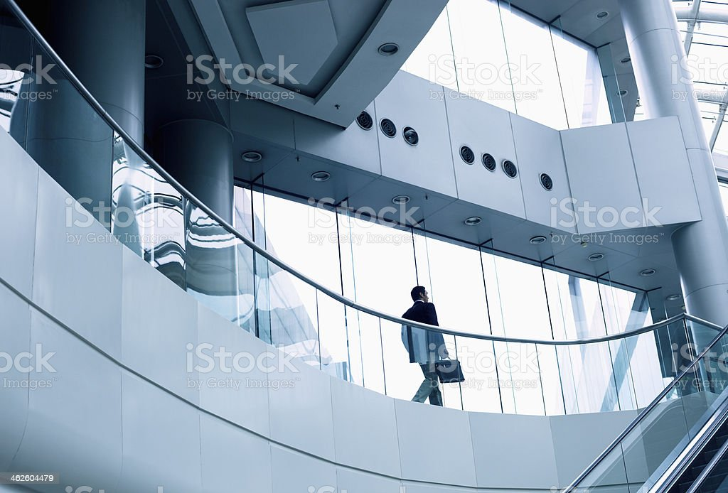 Distant businessman walking in a modern office building stock photo