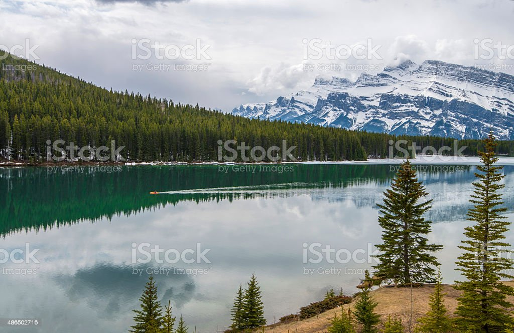Distant canoeist plys watercraft across lake, mountains stock photo