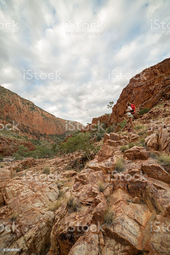 Distant female hiking in the Australia's outback stands on rock stock photo