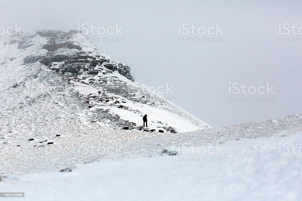 Distant Figure Climbing a Mountain Ridge stock photo
