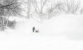 distant image of a man snow blowing his driveway.