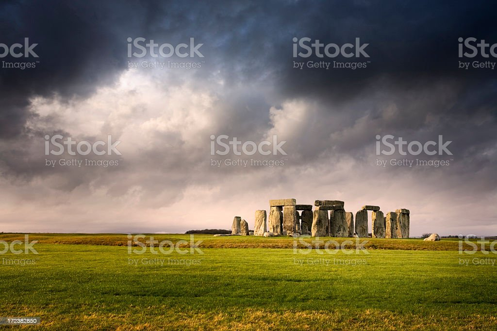 Distant overview of Stonehenge against stormy skies stock photo