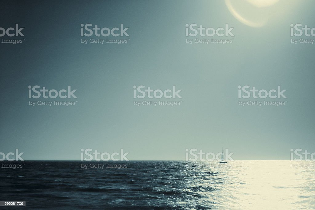 Distant sailing boat over the horizon with copyspace stock photo