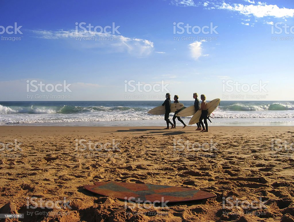A distant shot of friends going surfing at the beach stock photo