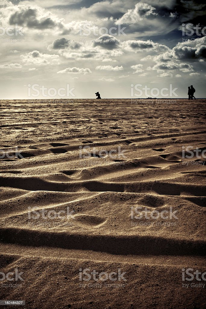 Distant silhouettes on the beach royalty-free stock photo