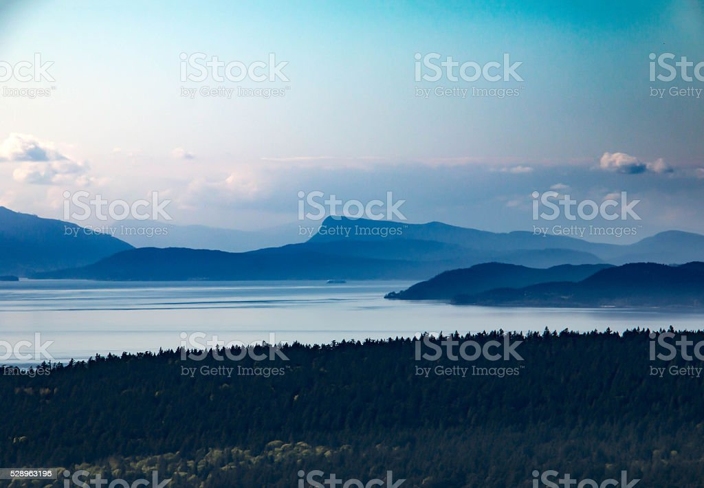 Distant view of blue mountains and ocean stock photo
