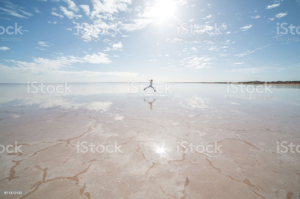 Distant woman jumping on salt lake stock photo