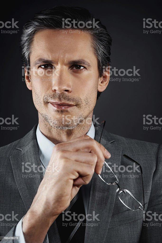 Distinguished executive holding eyeglasses royalty-free stock photo