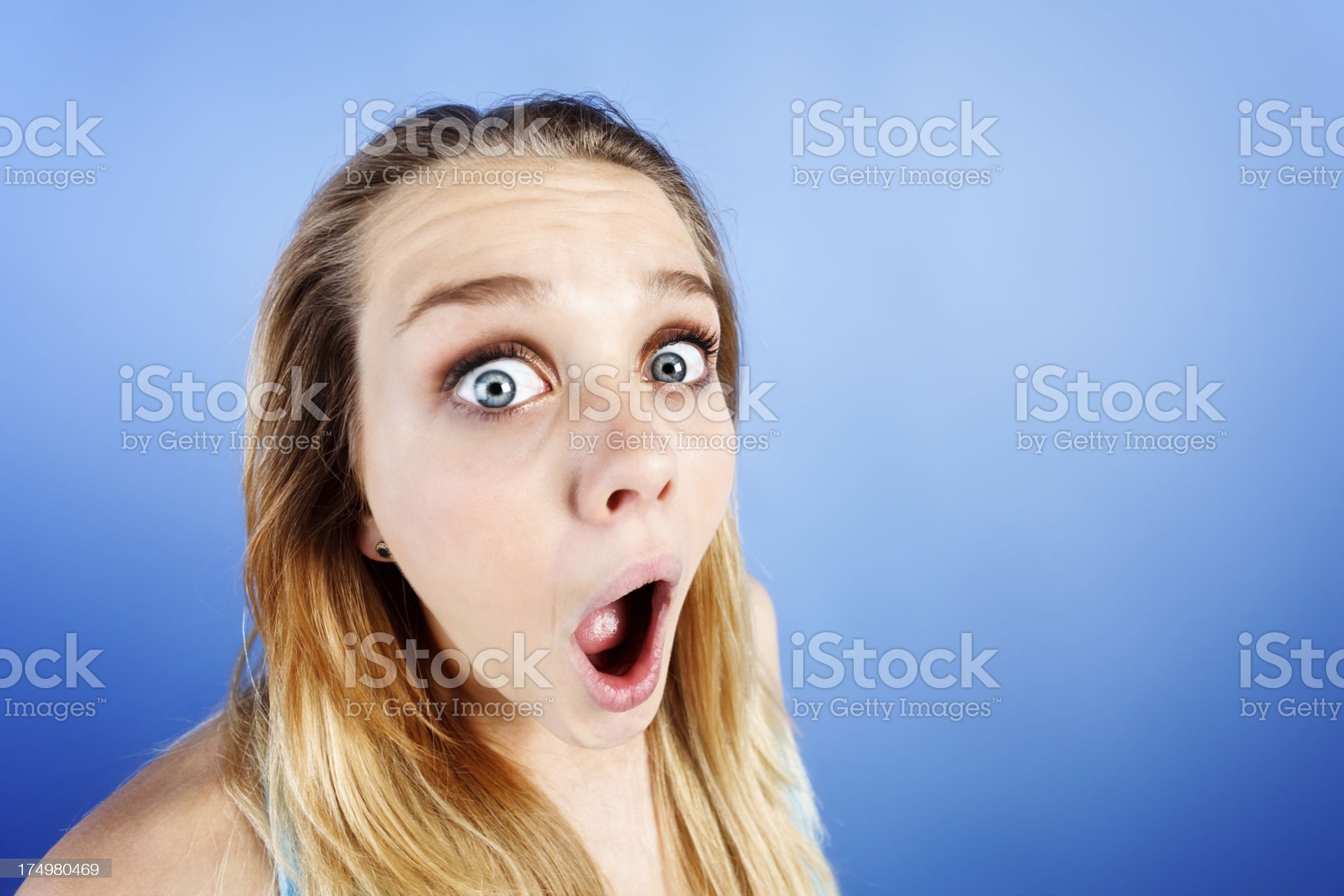 Distorted image of pretty teenager looking shocked on blue background royalty-free stock photo