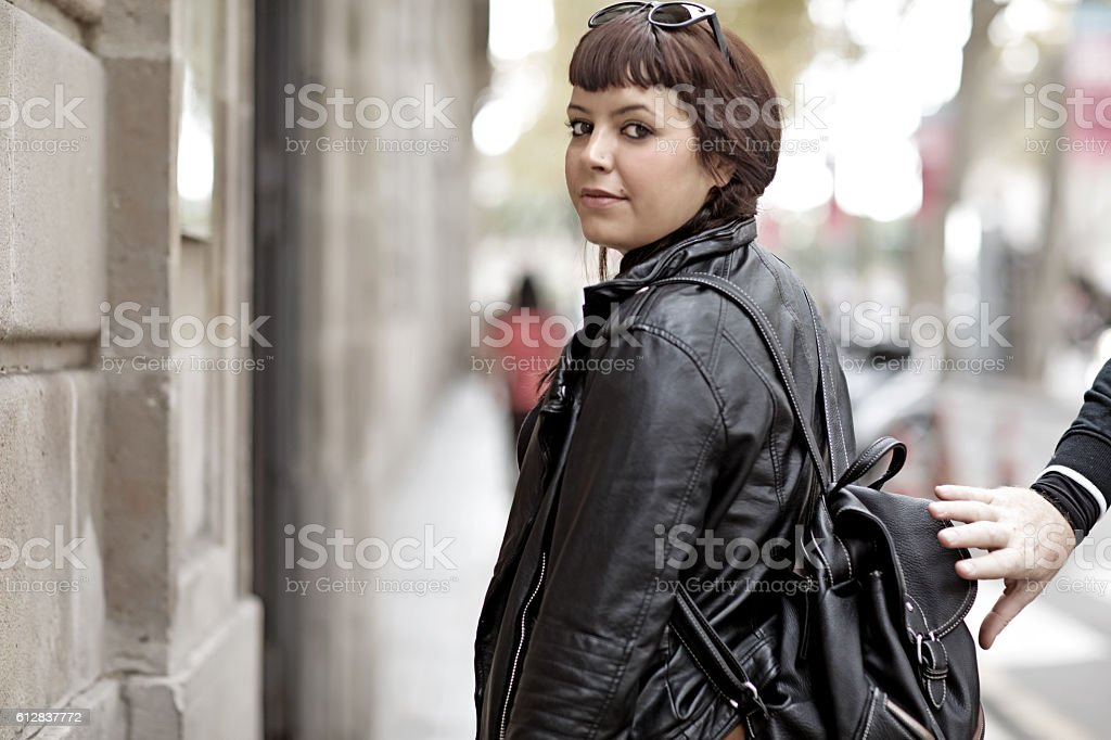 Distracted brunette female tourist and a pickpocket stock photo