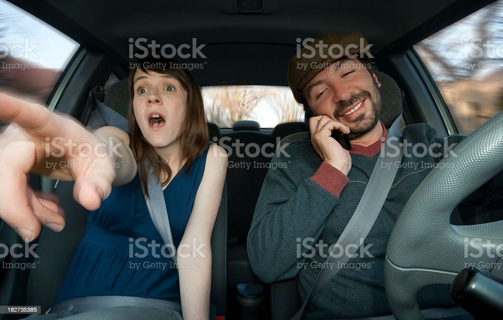 A distracted driver ignoring his passenger's warning stock photo
