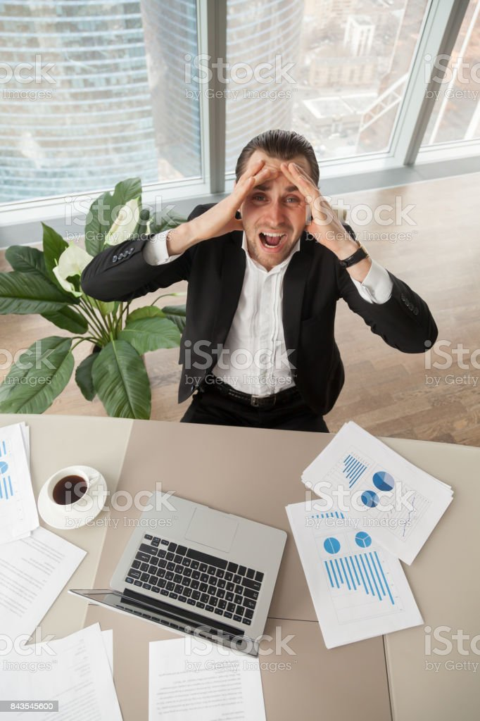 Distraught businessman at work looking up screaming in anger. stock photo