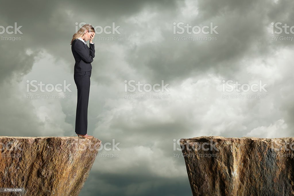 Distraught businesswoman standing at the edge of a cliff stock photo