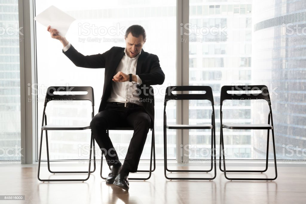 Distraught impatient businessman yelling in anger because of tedious wait. stock photo