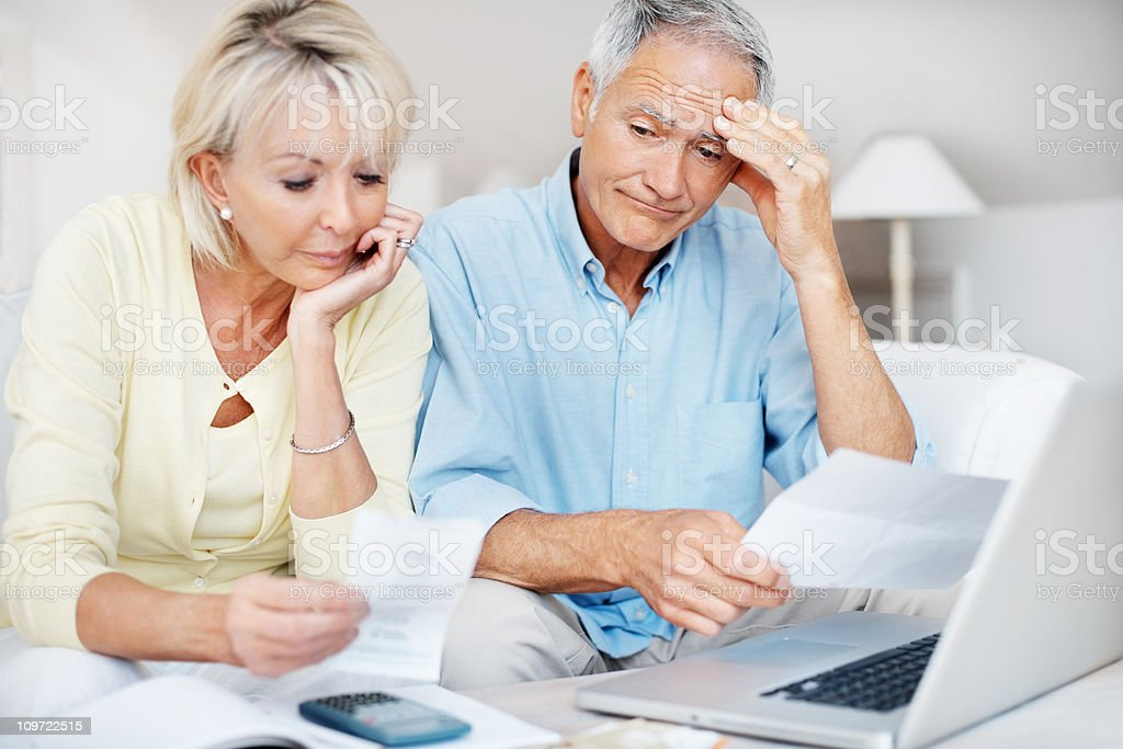 Distressed mature couple angry with so many bills to pay stock photo