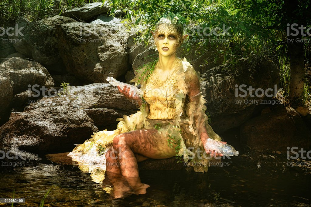 Distressed water nymph picks up plastic waste from stream stock photo