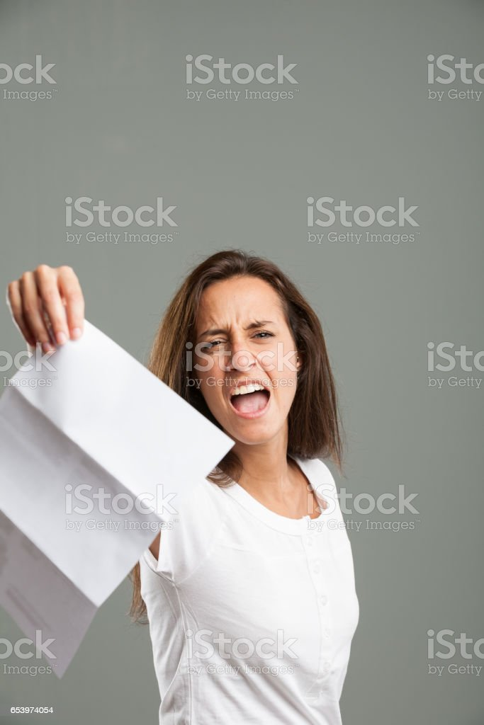 Distressed young woman holding up a document stock photo