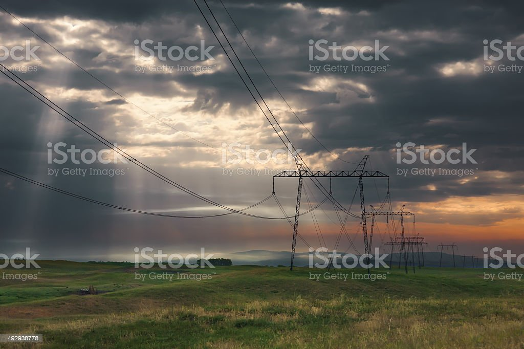 Distribution pylons with high voltage wires at sunrise stock photo