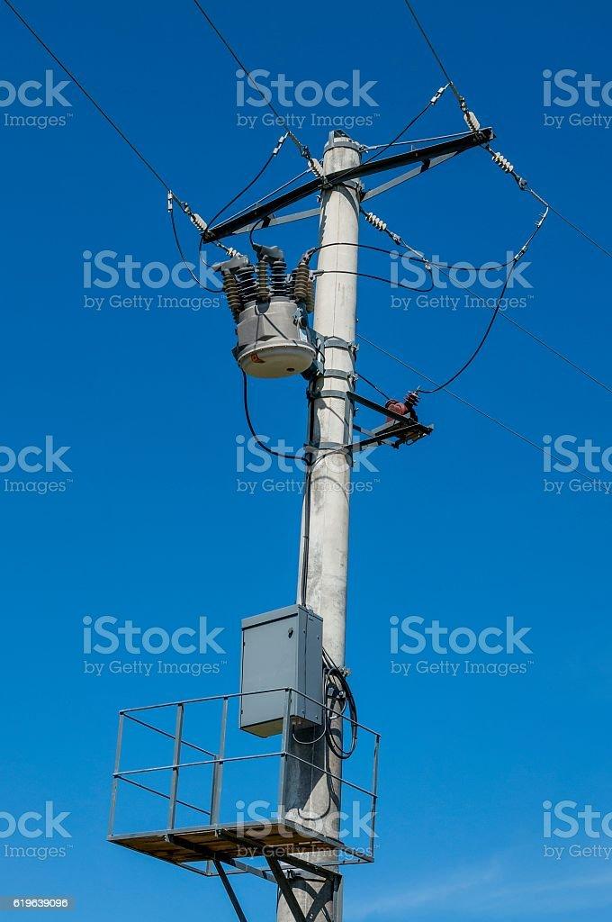 Distribution transformer on concrete power pole against blue sky stock photo