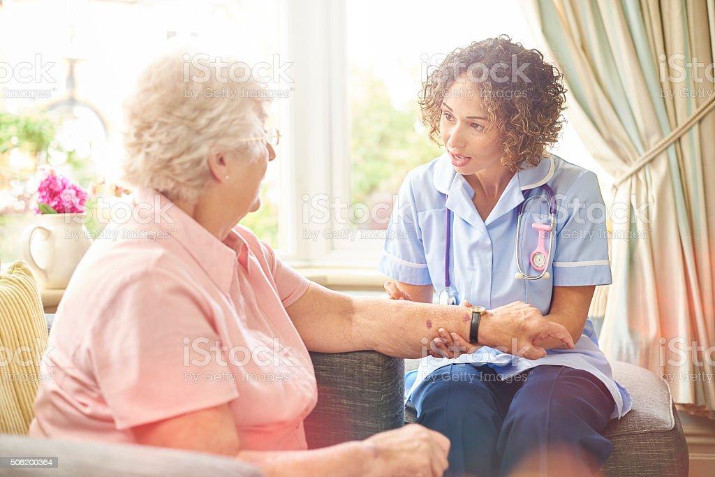 district nurse visit to senior woman stock photo