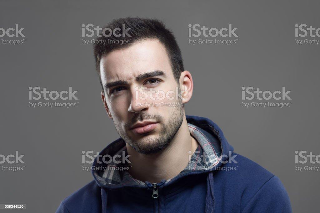 Distrustful young man looking dubious at camera stock photo