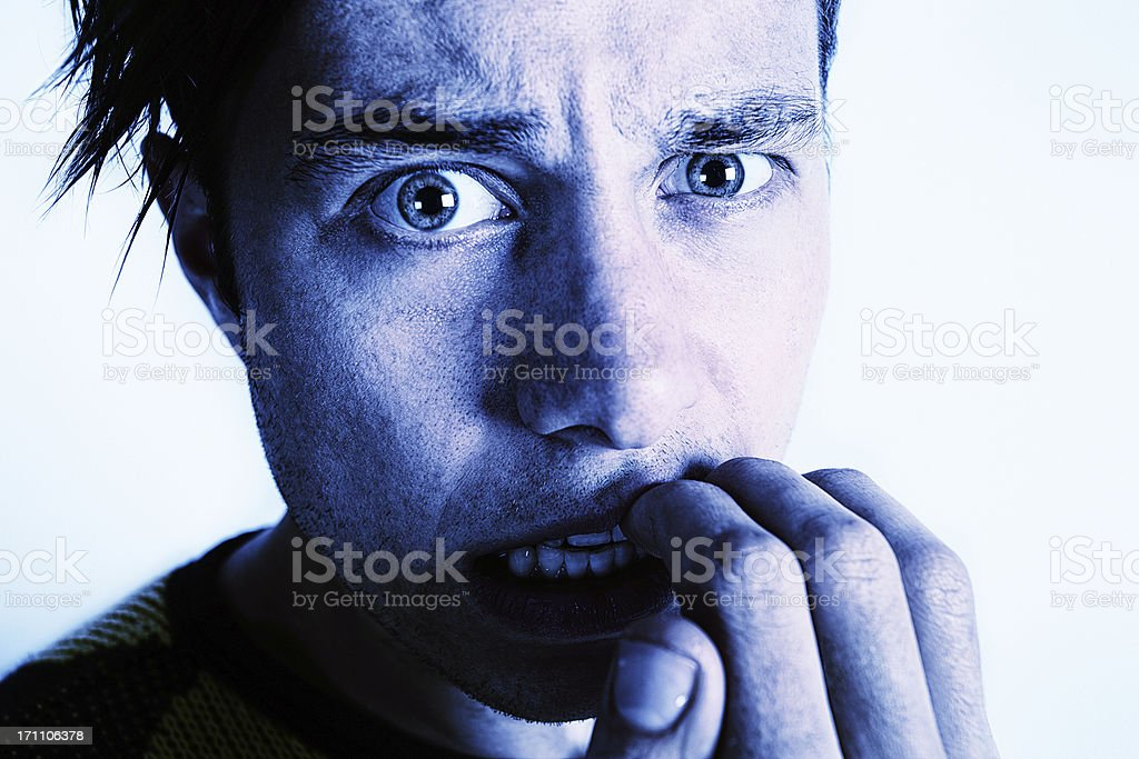 Disturbed looking young man biting nails and staring royalty-free stock photo