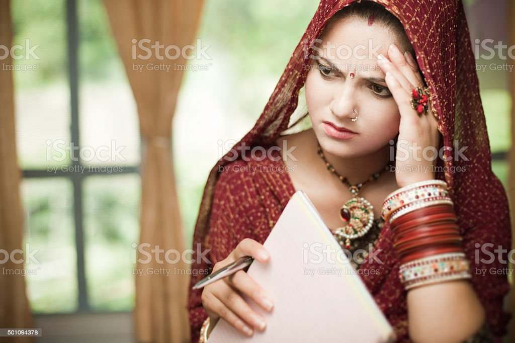 Disturbed newly married Indian, young woman holding pen and notepad. stock photo