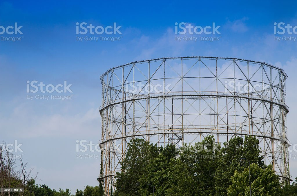 disused gasometer metal covered with vegetation stock photo