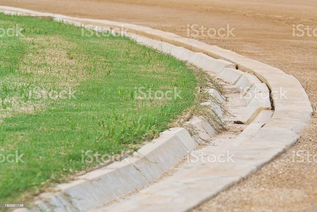 Ditch between  football field and racetrack royalty-free stock photo