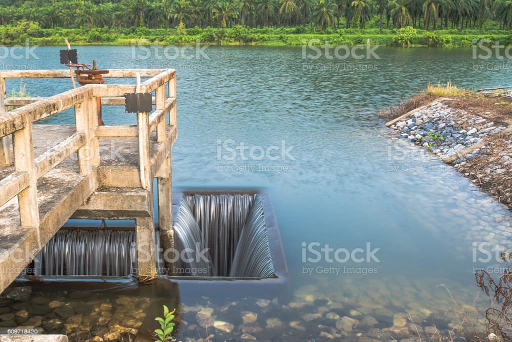 Ditch inlet of weir water gate infrastructure overflow from lake stock photo