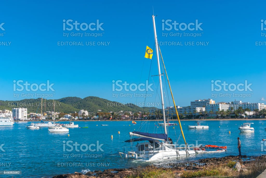 Dive crew works to recover crippled partially submerged catamaran boat. stock photo